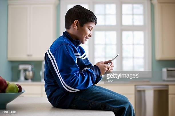 Boy Using Cell Phone in Kitchen