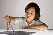 Boy (6-8) using compass, close-up