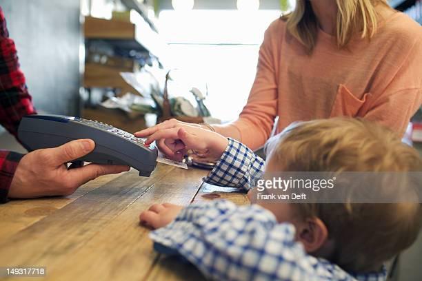 Boy using credit card machine in store