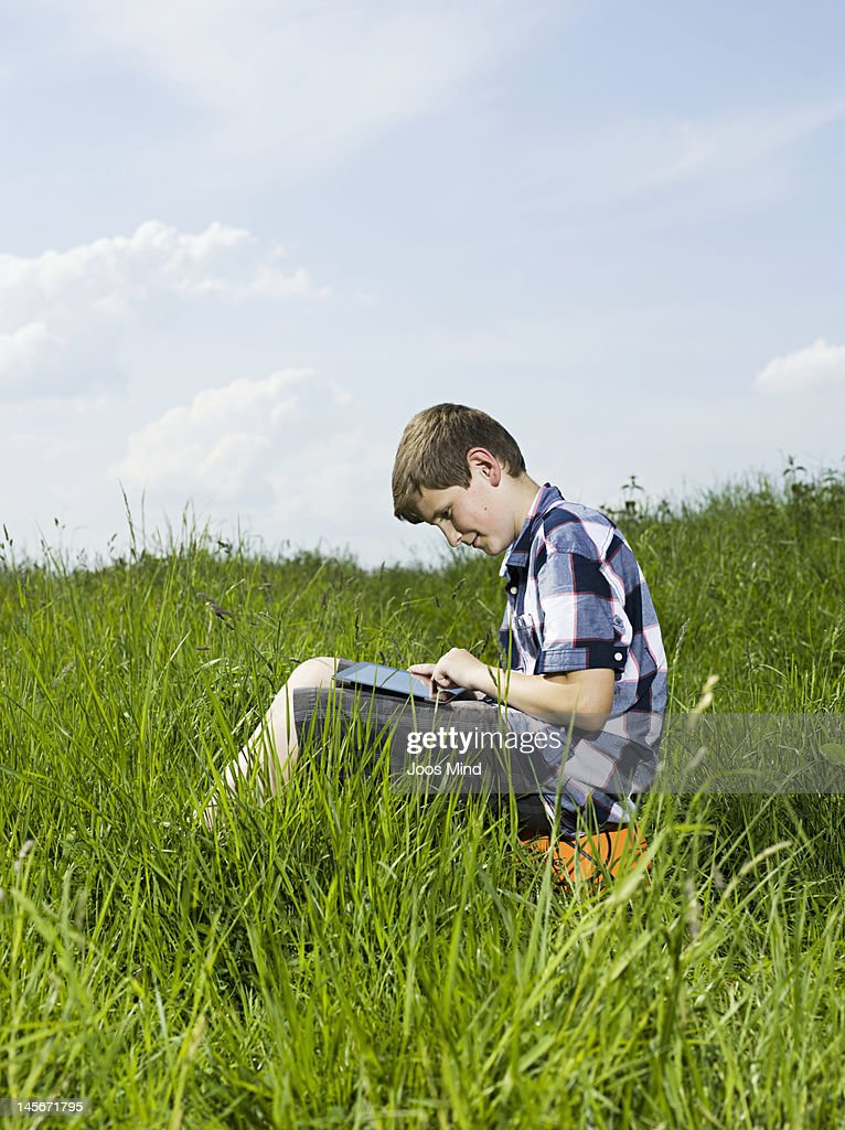 boy using digital tablet outdoors : Stock Photo