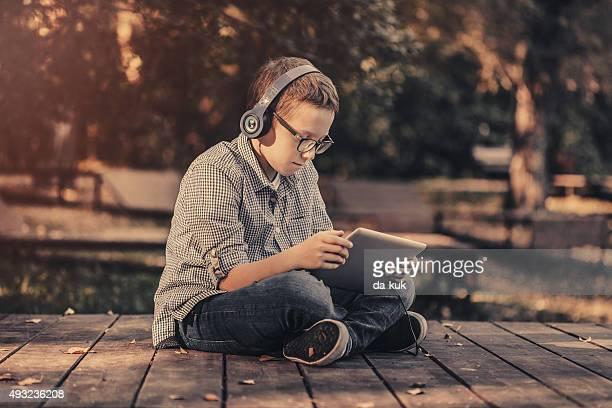 Ragazzo utilizzando la tavoletta digitale seduto nel parco