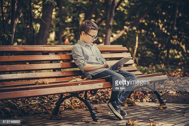 Boy using digital tablet sitting in the park