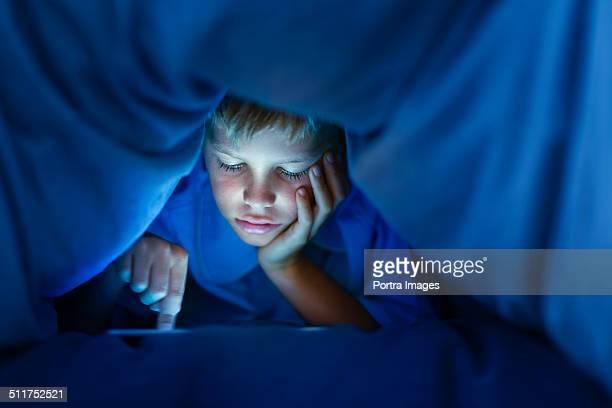 Boy using digital tablet under blanket