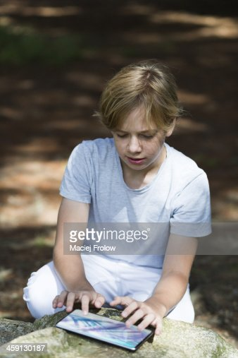 Boy using electronic device in a park : Stock Photo
