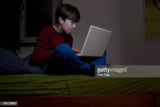 Boy using laptop in his room