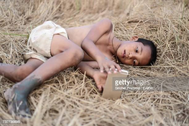 Boy Using Mobile Phone While Lying On Field At Farm