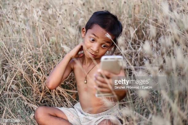 Boy Using Mobile Phone While Sitting On Field At Farm