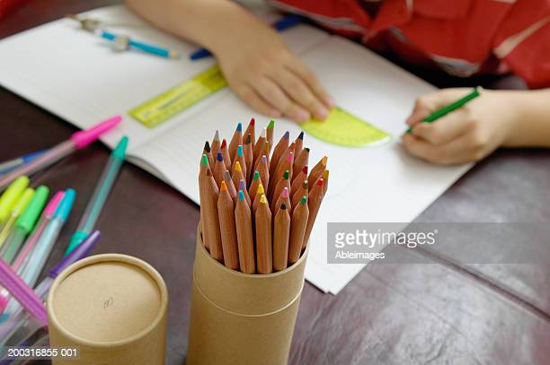 Boy (6-8) using protractor, focus on pot of pencils, close up
