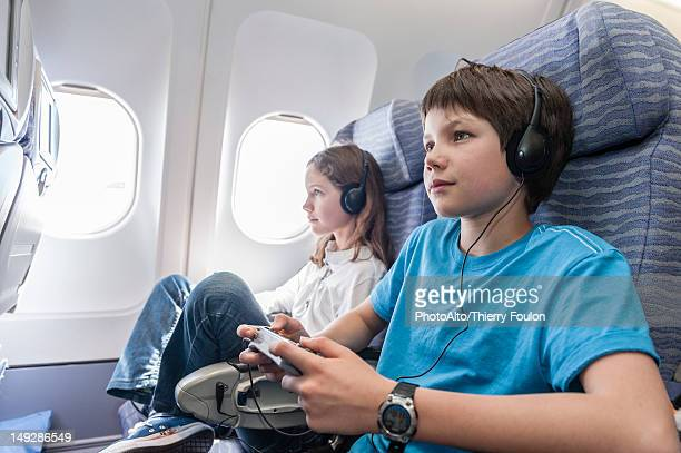 Boy using remote control to change channels on airplane