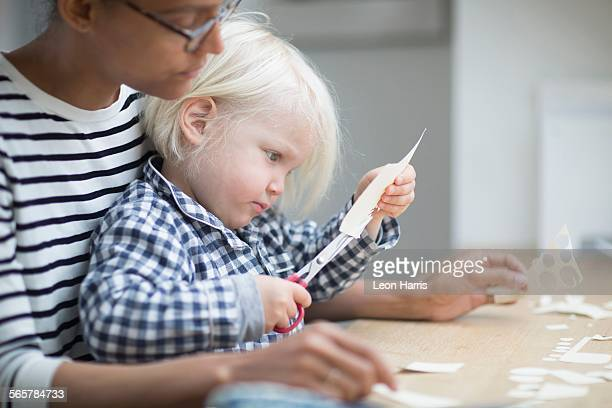Boy using scissors to cut paper with his mother