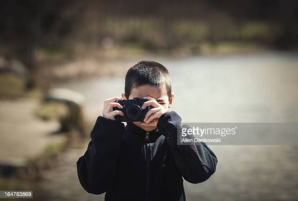 boy using small range finder camera outdoors