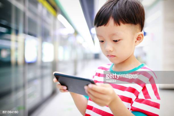 Boy Using Smart Phone on the subway