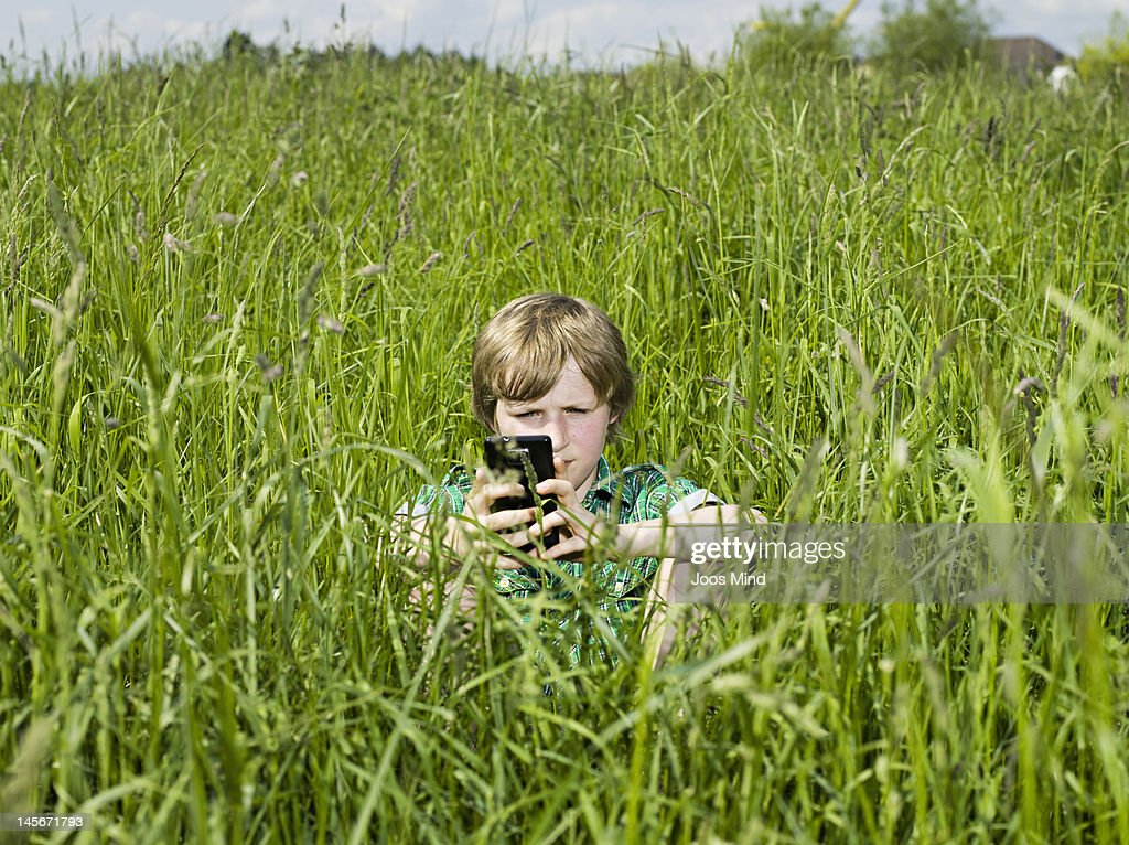 boy using smart phone outdoors : Stock Photo