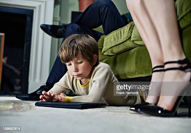 Boy using tablet computer under sofa