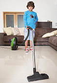 Boy (8-9) using vacuum cleaner in living room, portrait