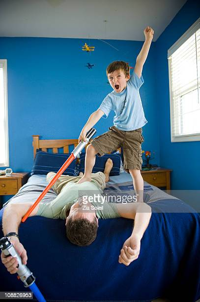boy vanquishing his dad with a light saber