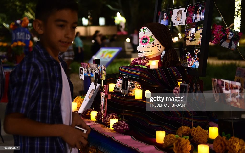 A boy views objects displayed on altars during a traditional Mexican celebration of 'Noche de Ofrenda' in downtown Los Angeles California on October...