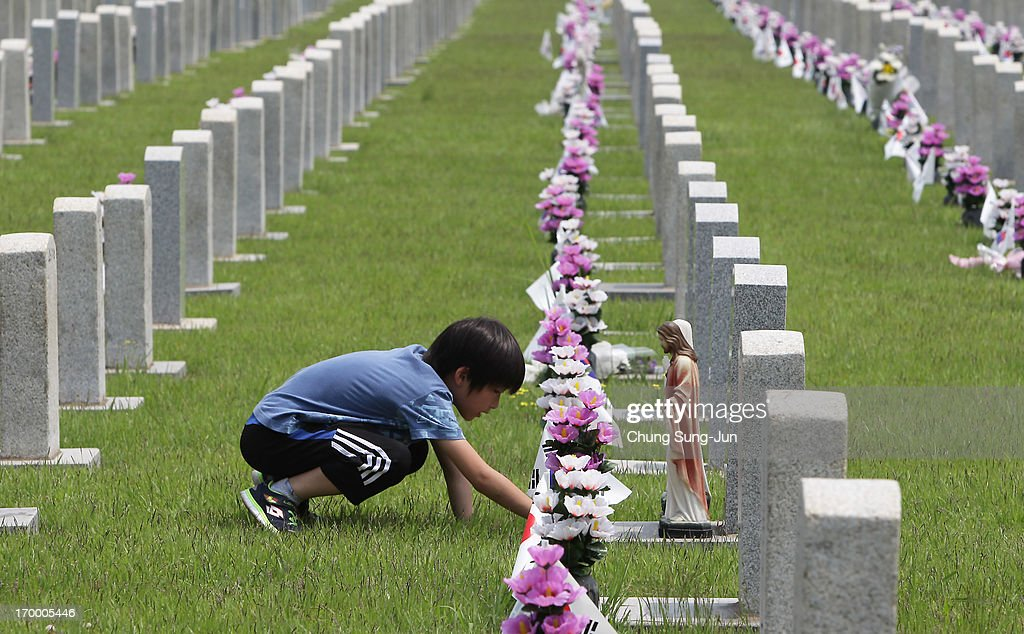 A boy visits the grave of his relative who died during the Korean War at Seoul National Cemetery on June 6, 2013 in Seoul, South Korea. South Korea today marks the 58th anniversary of the Memorial Day for those killed in the 1950-53 Korean War.