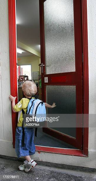 A boy waiting at a door for the first day of kindergarten