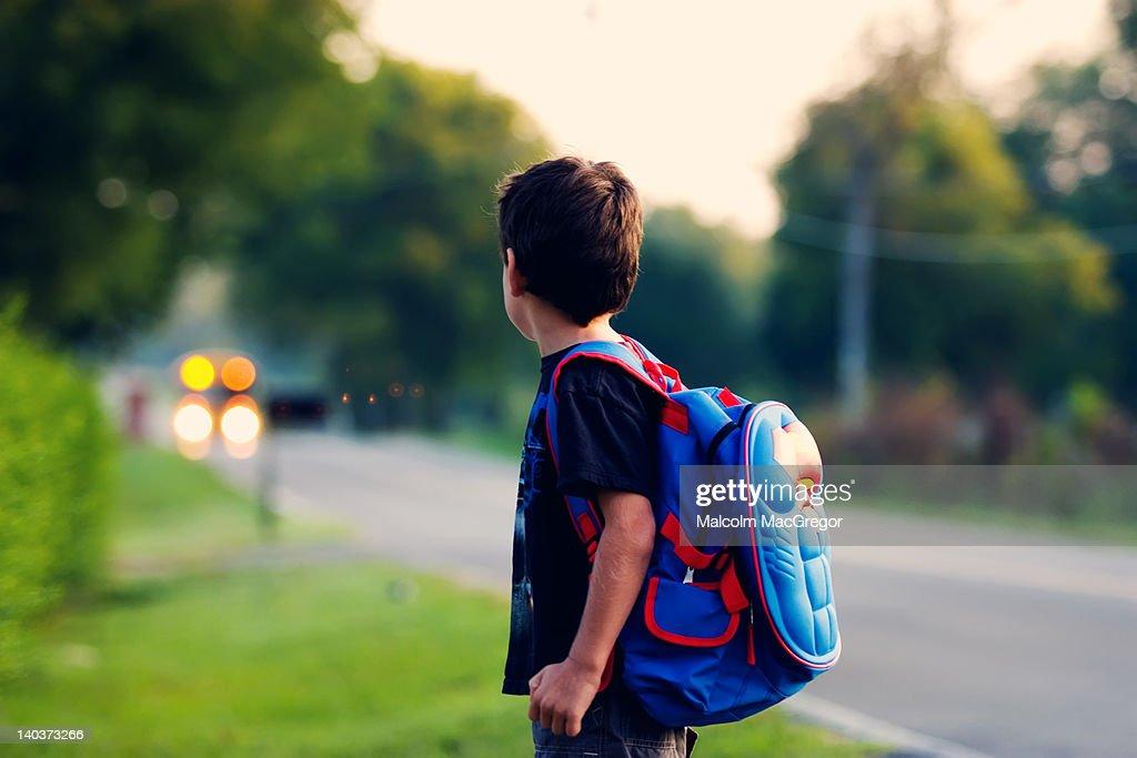 Boy waiting for school bus : Stock Photo