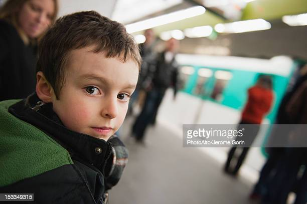 Boy waiting for train in subway station