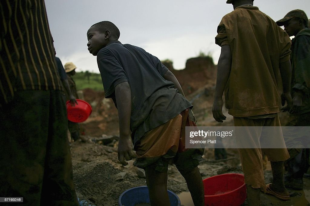A boy waits for a bucket which will be sifted through while looking for gold March 27, 2006 in Mongbwalu, Congo. Thousands of Congolese scrape together meagre livings from mining. Gold and other mineral deposits, which are numerous in the volatile north-east of the country, have become a catalyst to much of the conflict in Congo. The Democratic Republic of Congo (DRC), a country that loses an estimated 1,400 people per day due to war since 1998, is struggling to hold Presidential elections this summer. The volatile East of the country, which is situated hundreds of miles from the capital Kinshasa, has been the focal point of continued violence. Numerous militias and warlords have vied for control of the mineral rich eastern Congo for decades, creating instability and continued bloodshed.