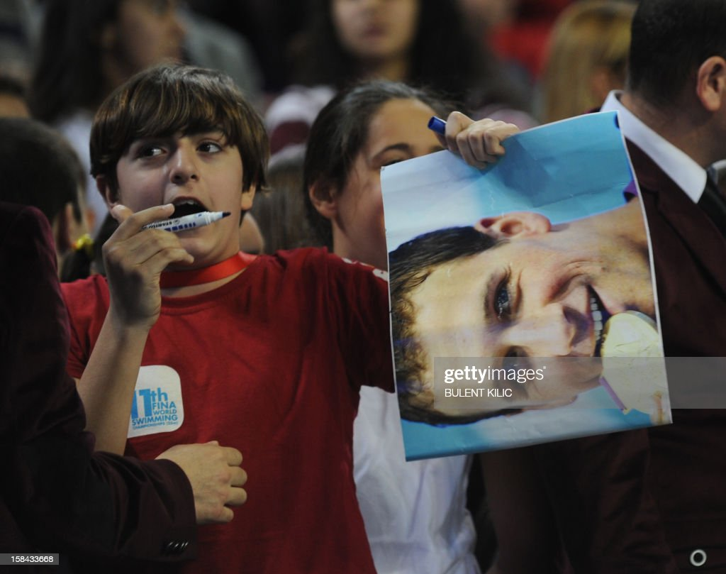 A boy waits for an autograph from Ryan Lochte of US during the Short Course Swimming World Championships in Istanbul on December 16, 2012. AFP PHOTO/BULENT KILIC