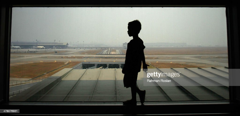 A boy waits for his family members arrival at Kuala Lumpur International Airport on March 12, 2014 in Kuala Lumpur, Malaysia. Officials have expanded the search area for missing Malaysia Airlines flight MH370 beyond the intended flight path to include the west of Malaysia at the Straits of Malacca as new information surfaces about the time Subang air traffic control lost contact with the aircraft. The flight carrying 239 passengers from Kuala Lumpur to Thailand was reported missing on the morning of March 8 after the crew failed to check in as scheduled.