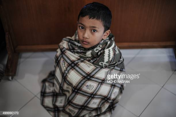 A boy waits his turn to take part in a mass circumcision ceremony at a mosque in Ampang in the suburbs of Kuala Lumpur on December 5 2015 About 200...