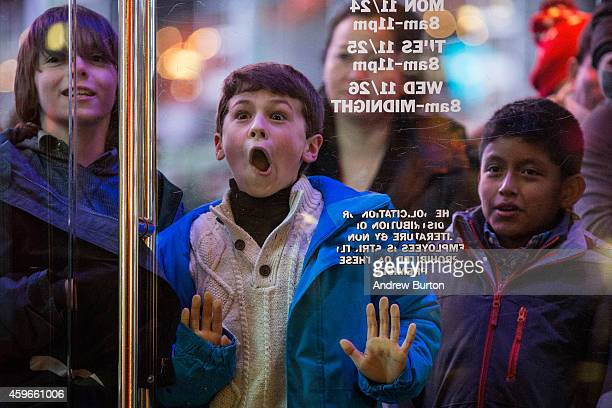 A boy waits to enter the Toys R Us in Times Square on November 27 2014 in New York United States Black Friday sales which now begin on the Thursday...