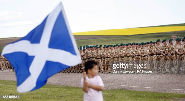 A boy waives the Scottish flag as members of 45 Commando Royal Marines who recently returned from a tour of duty in Afghanistan march through...