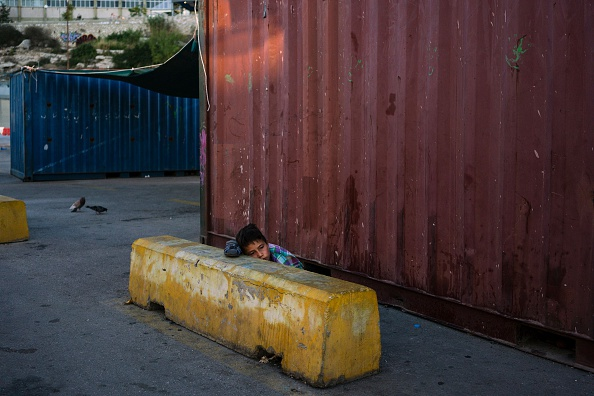 TOPSHOT - A boy wakes up in the port of Piraeus, where nearly 1,500 refugees and migrants live in a make-shift camp in Athens on July 17, 2016. In partnership with local aid groups Faros and Solida...