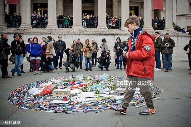 A boy walk with a pen towards the vigil at Trafalgar Square to show his respect to victims of the terrorist attacks in Paris on January 11 2015 in...