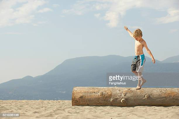 Boy walking across a log on the beach