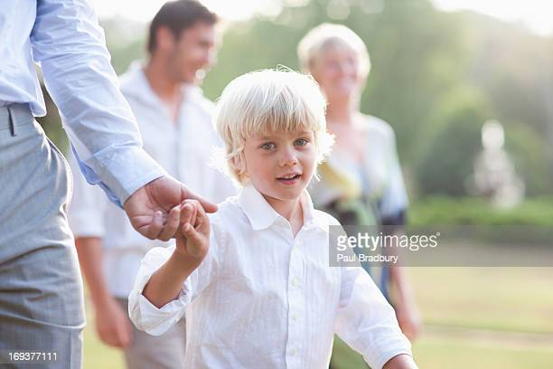 Boy walking across lawn at wedding