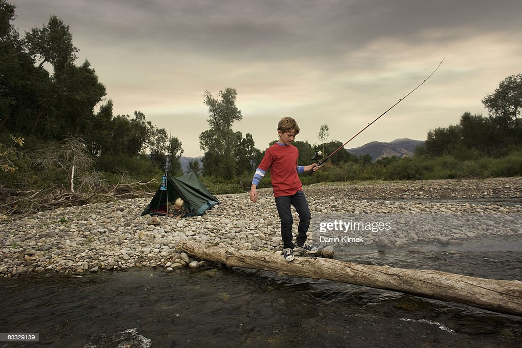 Boy walking across tree bride with fishing pole : Stock Photo