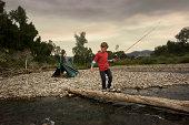 Boy walking across tree bride with fishing pole