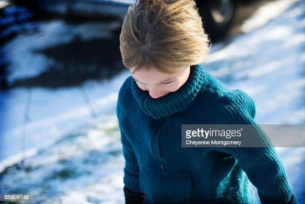 Boy walking against the wind.