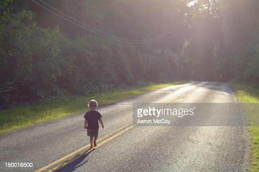 boy walking alone on road - photo #1