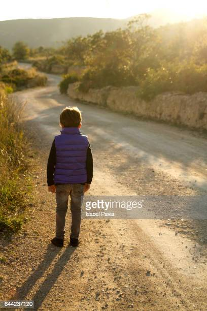 boy walking alone on road - photo #2