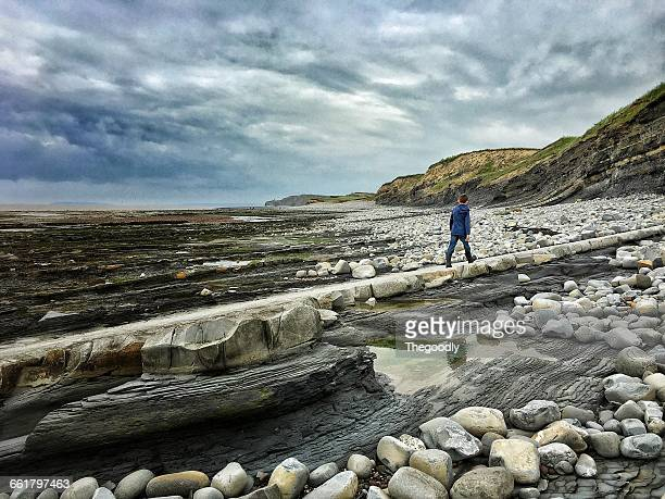Boy walking along beach, Ilve, Jurassic coast, somerset, england, UK
