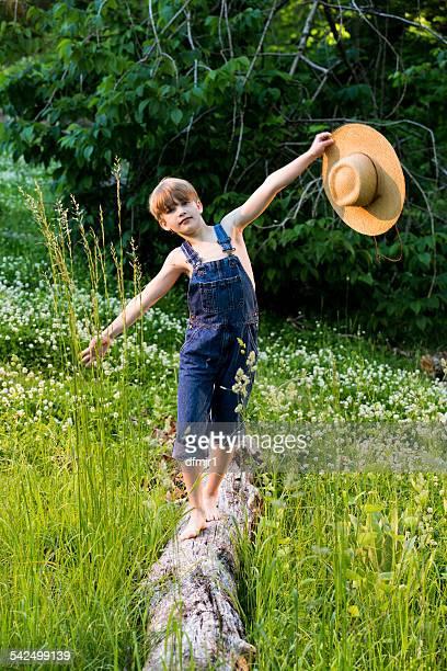 Boy walking along tree trunk in a meadow