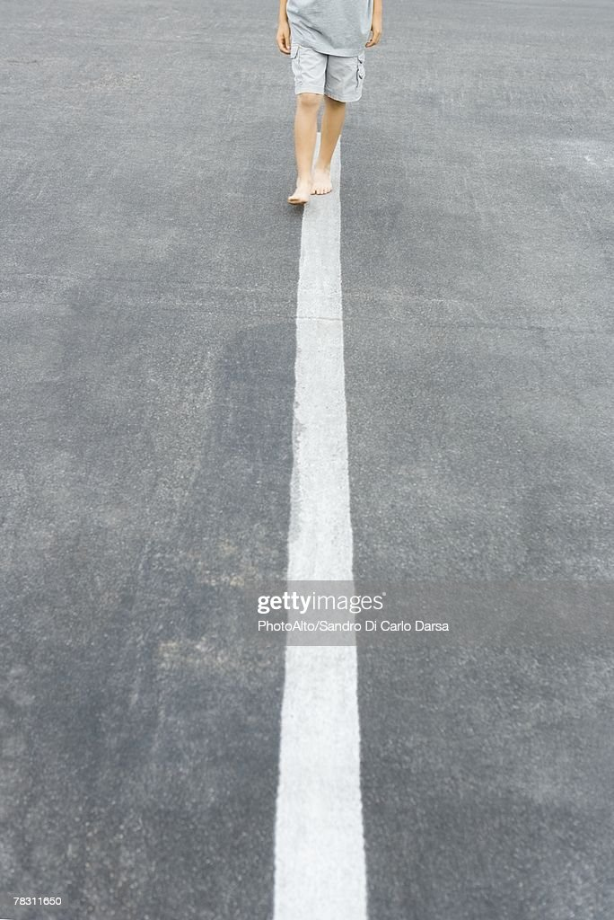 Boy walking along white dividing line, cropped view : Stock Photo