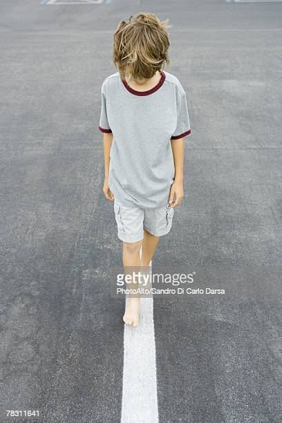 Boy walking along white dividing line, high angle view