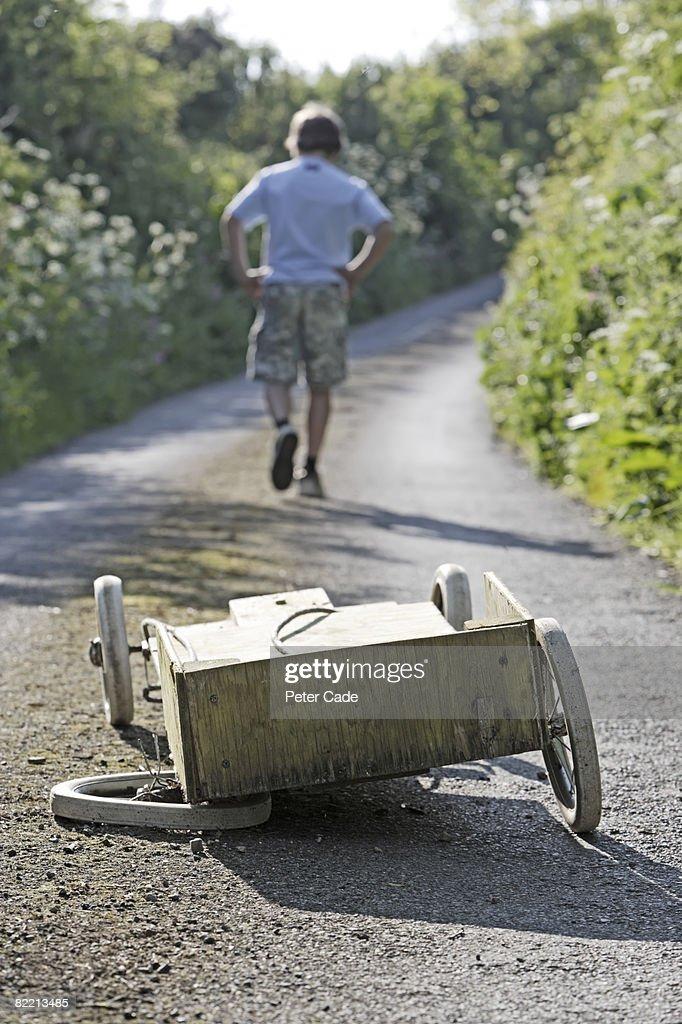 Boy walking away from broken go-kart : Stock Photo
