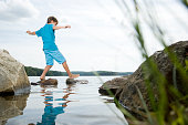 Boy walking barefoot across stones in lake