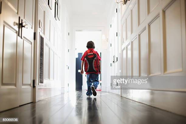Boy Walking in Hallway Wearing Backpack