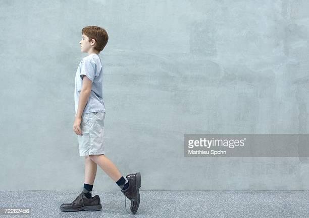 Boy walking in oversized shoes