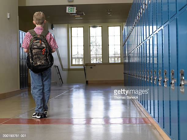 Boy (9-11) walking in school hallway, rear view