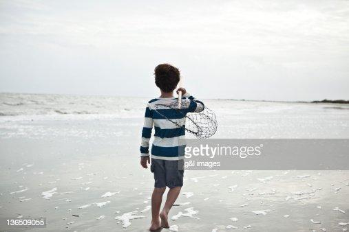 boy walking on beach with fishing net : Stock Photo